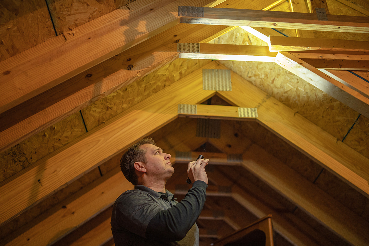Jon preforming home inspection services, including inspecting an attic with a flashlight.