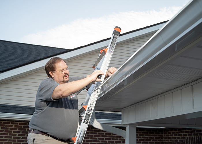 Home Inspector Gene on a ladder taking photos of a section of a roof.
