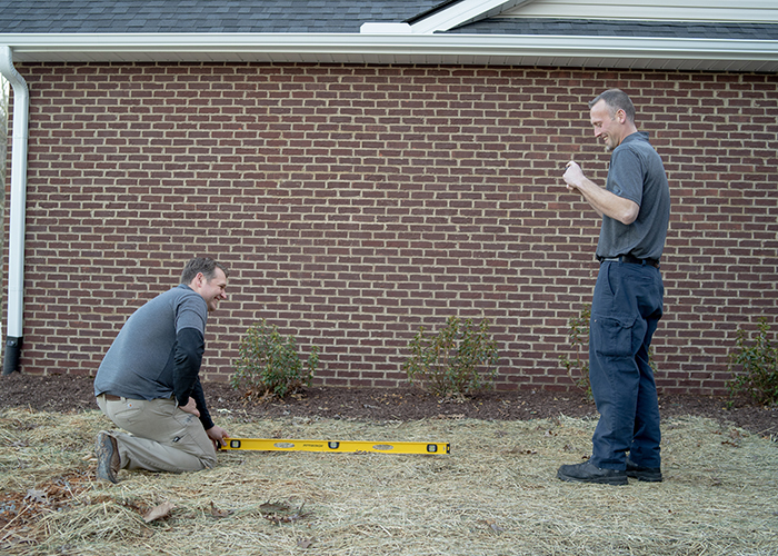 Jon and Tanner inspecting the foundation of a brick house.